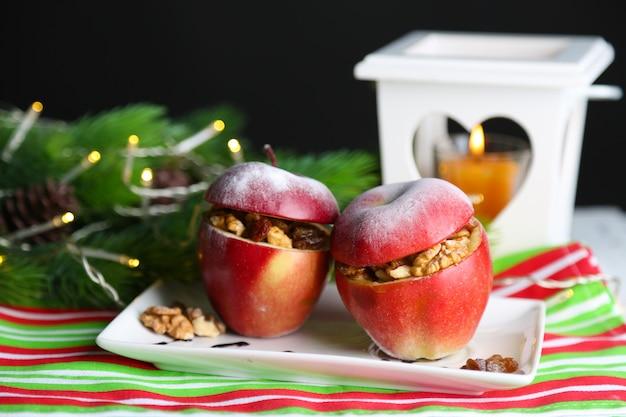 Gefüllte weihnachtsäpfel mit nüssen und rosinen auf dem tisch auf dunklem hintergrund