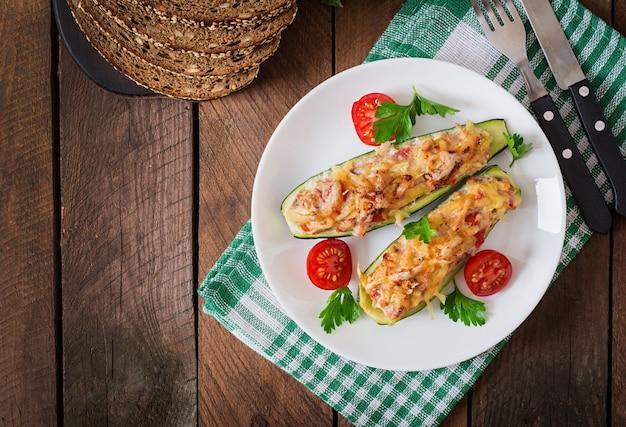 Gefüllte zucchini mit hühnchen, tomaten und zwiebeln mit käsekruste