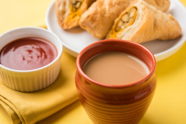 Gefüllter gemüsepuff oder samosa, berühmter indischer bäckereisnack, serviert mit tomatenketchup und heißem tee, selektiver fokus