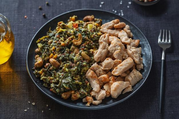 Gefüllter grünkohlsalat mit cashew und gekochter hühnerbrust serviert auf dunklem teller. gesunder lebensstil.