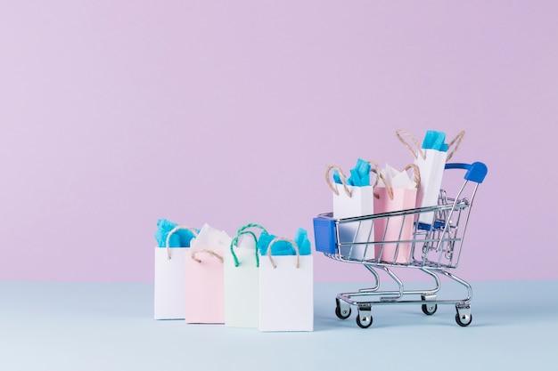 Gefüllter miniaturwarenkorb mit papiereinkaufstaschen vor rosa hintergrund