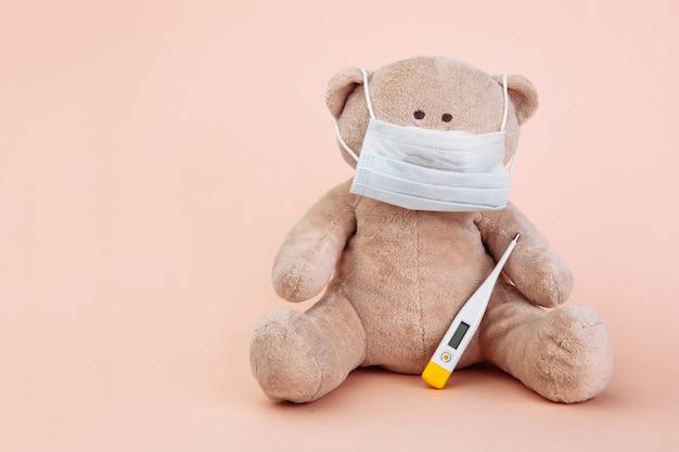 Gefülltes bärentier als kinderarzt mit auf rosa isolierten arztwerkzeugen vorgestellt.