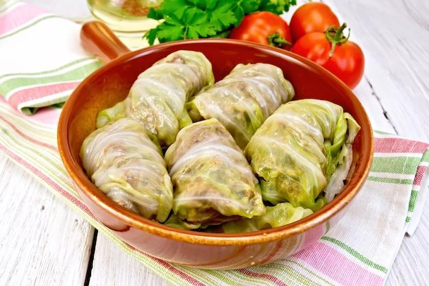 Gefülltes kohlfleisch in kohlblättern in einer keramikpfanne auf einer serviette, tomaten, petersilie auf einem helleren hintergrund aus holzbrettern