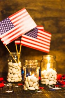 Gefülltes süßigkeitsglas mit brennenden kerzen und usa-flaggen auf holztisch