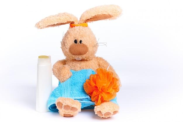 Gefülltes weiches kaninchen in einem blauen handtuch mit einem gummi an den ohren und mit duschzubehör.