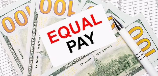 Gegen die oberfläche von berichten und dollars - ein weißer stift und eine karte mit dem text equal pay