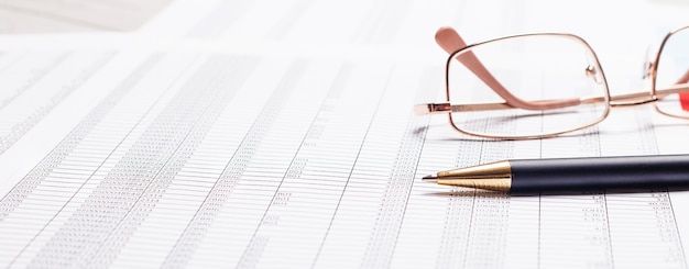 Gegen die oberfläche von dokumenten - stift und brille in goldrahmen