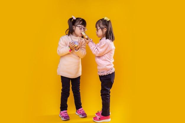 Gegen gelbe wand. nettes kleines mädchen, das geschwollenen donut trägt, während ihre schwester daran interessiert schnüffelt