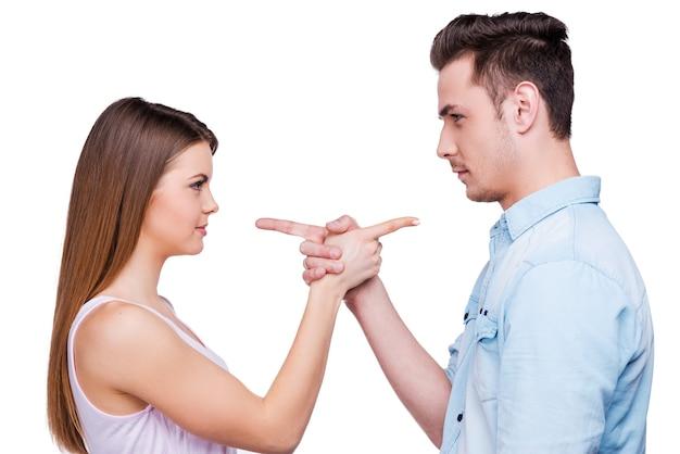 Gegenseitige ansprüche. seitenansicht eines schönen jungen liebespaares, das sich gegenseitig zeigt, während es vor weißem hintergrund steht