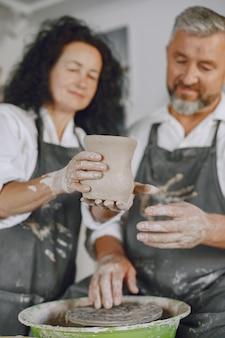 Gegenseitige kreative arbeit. erwachsenes elegantes paar in freizeitkleidung und schürzen. leute, die eine schüssel auf einer töpferscheibe in einem tonstudio schaffen.