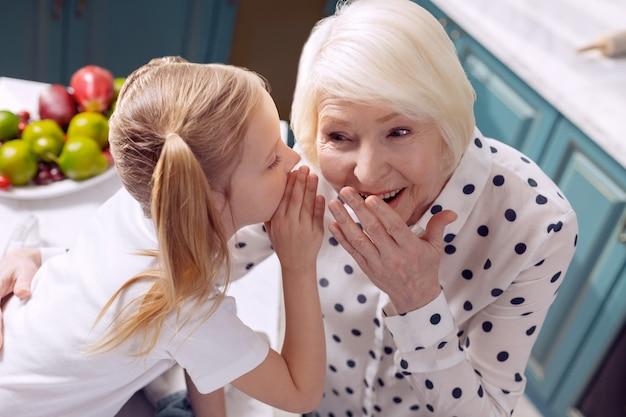 Gegenseitiges vertrauen. die draufsicht auf ein schönes kleines mädchen und ihre geliebte großmutter, die in der küche sitzen, geheimnisse teilen und sie miteinander flüstern