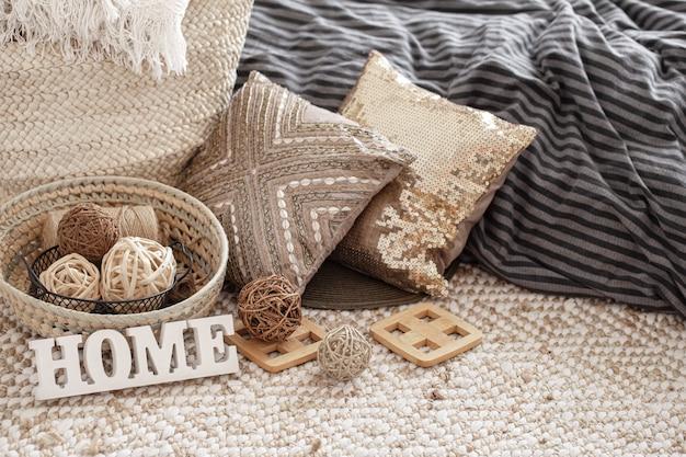 Gegenstände eines gemütlichen wohnraums mit kissen und einem holzschild nach hause