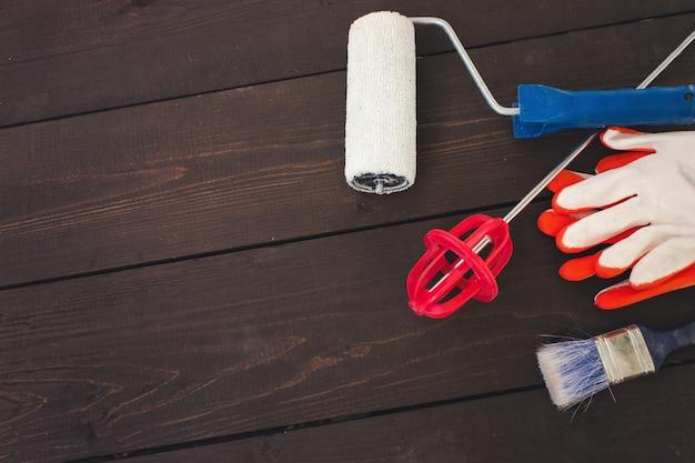 Gegenstände und werkzeuge des professionellen malers auf hölzernem hintergrund. maler- und dekorateurarbeitstisch