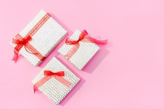 Gegenwärtiger hintergrund. geschenke auf rosa hintergrund. flache lage, draufsicht, kopienraum