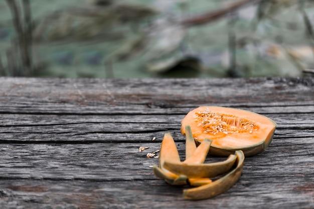 Gegessene und halbierte moschusmelone auf verwittertem holztisch