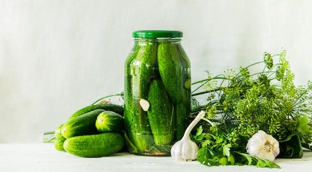 Gegorene oder einmachende gurken im glasgefäß auf tabelle verarbeitung der herbsternte. dosen essen