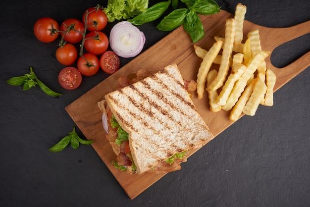 Gegrillt und sandwich mit speck, spiegelei, tomate und salat auf holzschneidebrett serviert