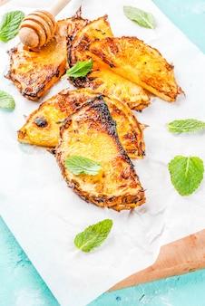 Gegrillte ananasscheiben mit minzhonig und limettensauce auf hellblauem hintergrund