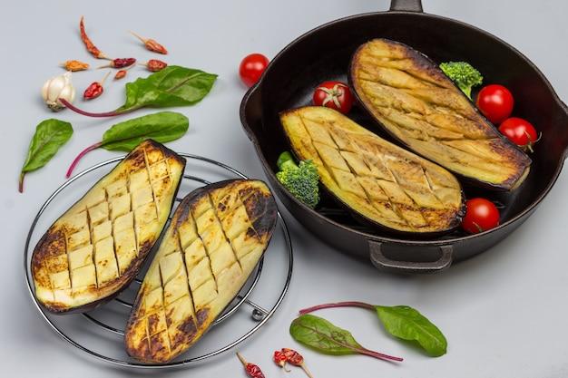 Gegrillte auberginen auf rost und in der pfanne. mangoldblätter und knoblauch auf dem tisch.