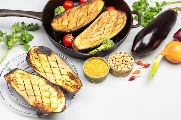 Gegrillte auberginen auf rost und in einer pfanne mit gemüse und grütze