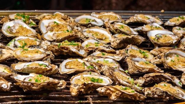 Gegrillte austern mit reisfüllung und kräutern werden auf dem chinesischen markt als beliebter schneller snack für touristen verkauft.