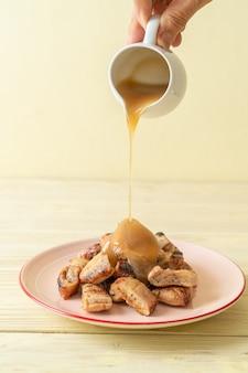 Gegrillte bananen mit kokos-karamell-sauce auf teller