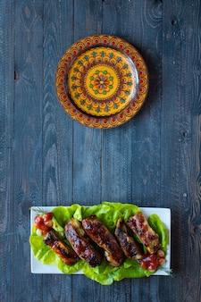 Gegrillte barbecue-schweinerippchen mit gemüse auf holzuntergrund; freiraum vor text.