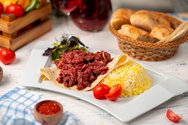 Gegrillte bbq-rindfleischscheiben, döner in lavash mit grünem salat, tomaten und reisgarnitur