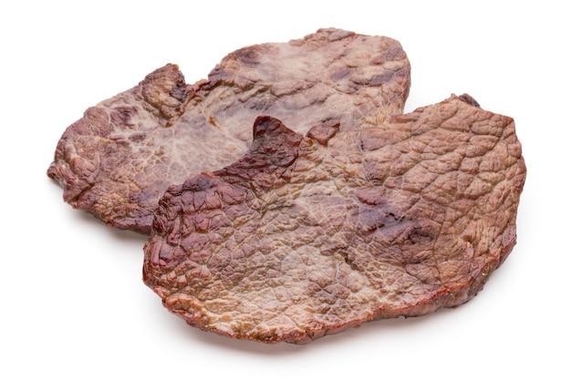 Gegrillte bio-rindfleischsteaks mit gewürzen lokalisiert auf weißem hintergrund.