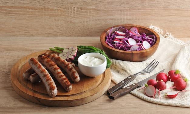 Gegrillte bratwurst mit sauce, spinat und knoblauch, ein radieschensalat