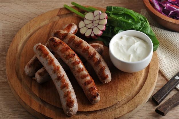 Gegrillte bratwurst mit sauce, spinat und knoblauch