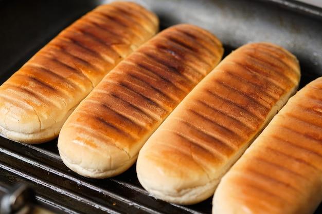 Gegrillte brötchen. zutaten für hotdogs. kochprozess für hotdogs. fast food.