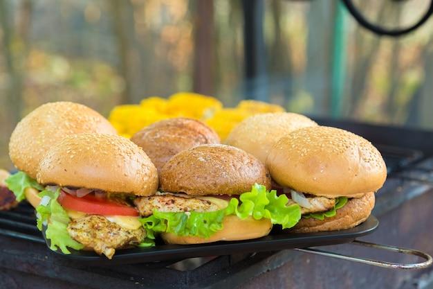 Gegrillte burger im freien. mit käse, zwiebeln, salat, tomate
