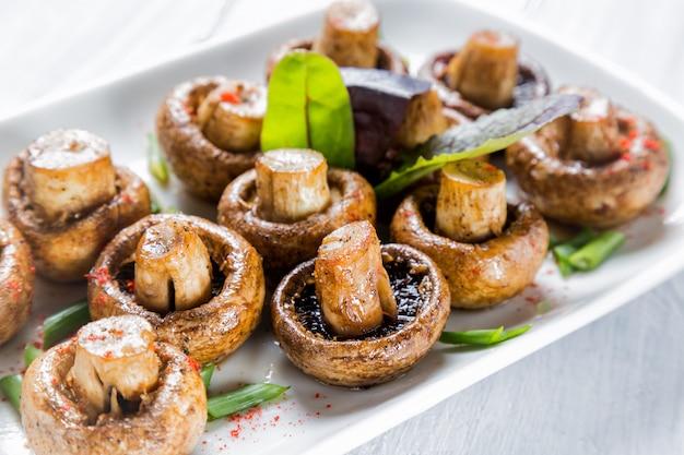 Gegrillte champignonweißpilze auf weißer platte mit kräutern und gewürzen