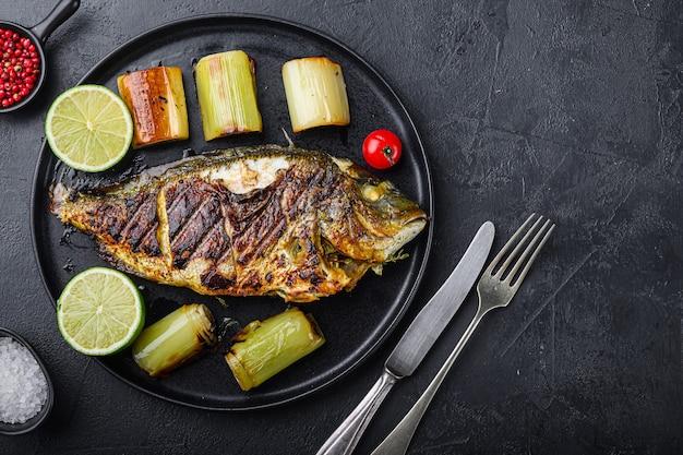 Gegrillte dorade oder dorado roher fisch auf schwarzem teller mit geschmortem lauch