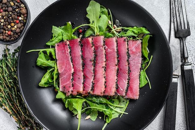 Gegrillte fisch-thunfisch-steakscheiben in einem teller mit rucola-salat. weißer hintergrund. draufsicht.