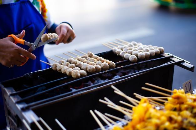 Gegrillte fleischklöschen auf grill greifen köstliche gebratene thailändische art des aperitifs ineinander