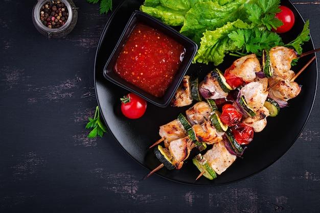 Gegrillte fleischspieße, hähnchen-schaschlik mit zucchini, tomaten und roten zwiebeln. barbecue essen.
