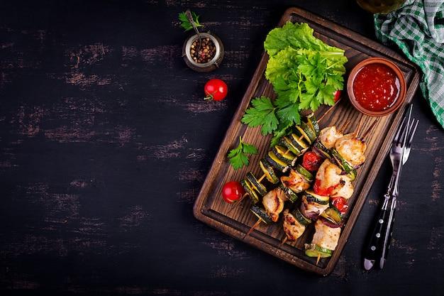 Gegrillte fleischspieße, hähnchen-schaschlik mit zucchini, tomaten und roten zwiebeln