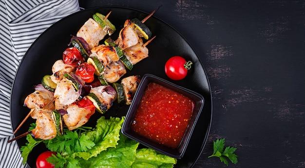 Gegrillte fleischspieße, hühnchen-schaschlik mit zucchini, tomaten und roten zwiebeln