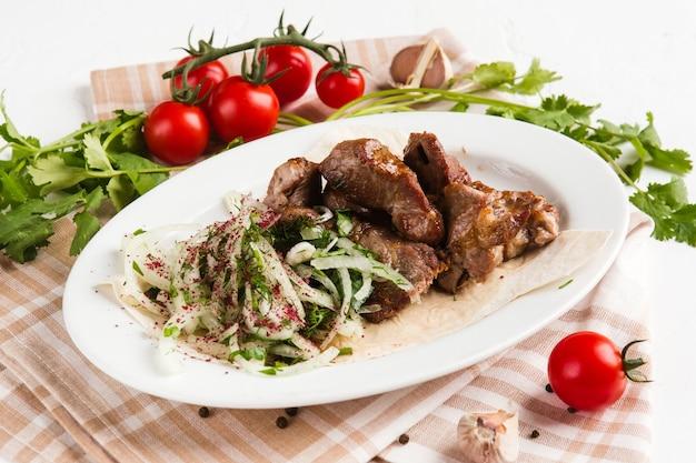Gegrillte fleischstücke auf einem weißen teller mit kräutern und gemüse
