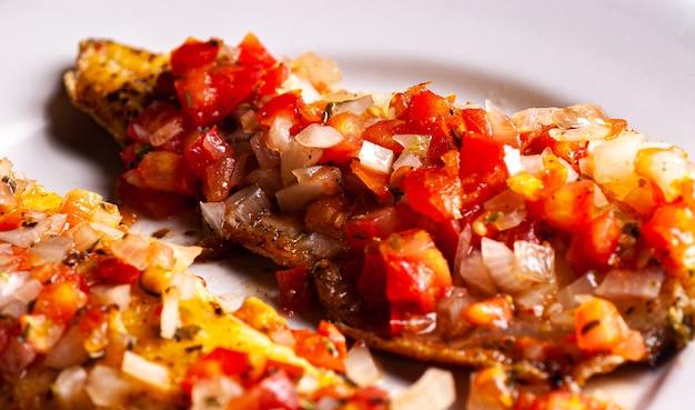 Gegrillte forelle in tomatensauce mit zwiebeln und pfeffer. im hintergrund karotten-, kohl- und gurkensalat.