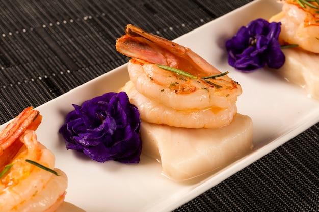 Gegrillte garnelen mit rohem nagelfisch auf weißem teller am tisch