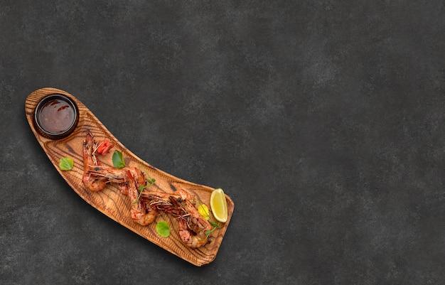 Gegrillte garnelen mit zitronensauce auf holzbrett auf grauem hintergrund mit platz für text draufsicht