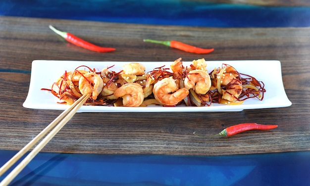 Gegrillte garnelen mit zwiebeln und chili auf einem weißen teller