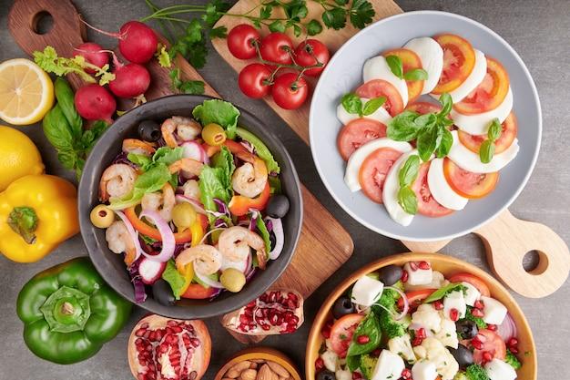 Gegrillte garnelen und frischer gemüsesalat. gesundes essen. flach liegen. italienischer caprese-salat mit tomaten, basilikum, mozzarella, traditionellen italienischen caprese-salatzutaten. mediterraner, griechischer salat.