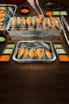 Gegrillte garnelen und muscheln auf holzkohle mit frischen meeresfrüchten und pikanter sauce.