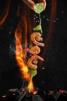 Gegrillte garnelen- und muschelspieße über kohlenhitze auf feuer- und rauchhintergrund