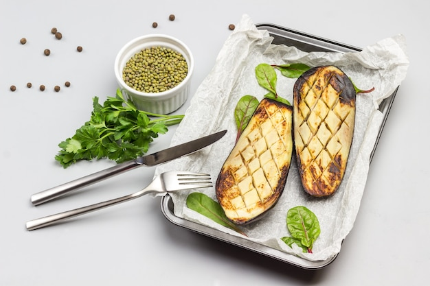Gegrillte gebackene auberginen auf palette gabel und messer maische in schüssel und petersilienzweigen