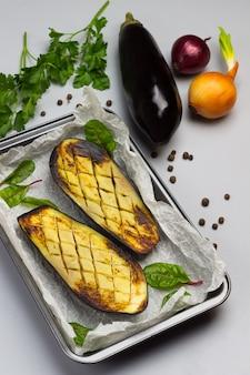 Gegrillte gebackene auberginen auf palette. ganze auberginen, zwiebeln und petersilie auf dem tisch.